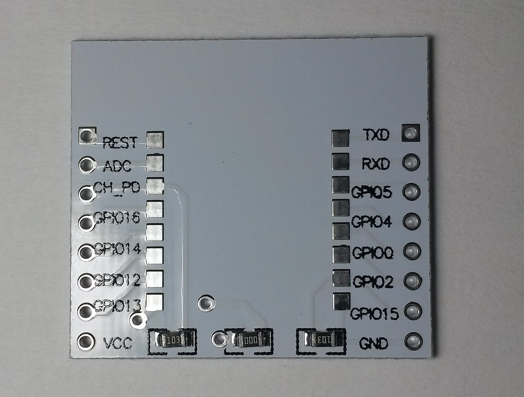 Minimal ESP-12 breakout - top side. You can see a 10k pull-up on CH_PD (enable) pin, 10k pull-down on GPIO15 and a 0R connection bridging the voltage regulator on the other side of the board.